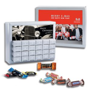 Der Adventskalender Exquisit hat 24 Geschenkboxen, die gefüllt sind mit Mniatures Mix oder Lindt Hello Mini Sticks. Weiterhin kann die Vorderseite des Kalenders individuell bedruckt werden.