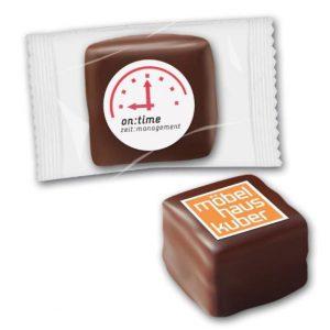 Ein Dominostein mit Logo auf der Oberseite. Der Dominostein wird individuell bedruckt mit Lebensmittelfarbe. Einzeln verpackt in transparenter Folie.