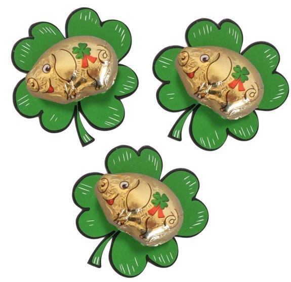 Schweinchen aus Schokolade aufgeklebt auf einem Kleeblatt aus Karton. Das Kleeblatt wird auf der Rückseite mit einem Werbeetikett versehen.