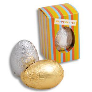 Schoko Osterei in Box 30g mit individuellem Druck auf der Verpackung. Die Verpackung hat ein Fenster sodass das Osterei zu sehen ist. Die Ostereier gibt es in silberner oder goldener Stanniolfolie.