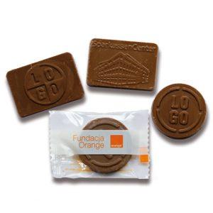 Die Schokotäfelchen mit Prägung 9g sind eine Marke der Firma Barry Callebaut. Die Schokolade kann individuell geprägt werden. Ebenfalls kann die Folie mit Logo bedruckt werden. Es gibt transparente oder Weiße Folie mit individuellem Druck.