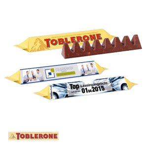 Toblerone im Werbeschuber 100g mit individuell nach Kundenwunsch bedruckter Banderole aus Karton.
