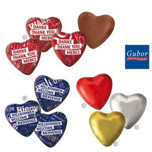 Schoko Herzen standard 8,5g mit Standarddruck. Verschiedene Designs mit Aufdruck Danke oder Willkommen oder aber in roter, silberner oder goldener Folie ohne Aufdruck.