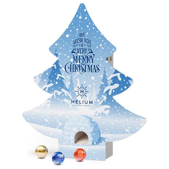 Der Adventsspender Baum ist mit Lindor-Kugeln gefüllt und kann individuell bedruckt werden. Der Adventsspender Baum hat eine Spenderöffnung auf der Vorderseite durch die die Kugel fällt.