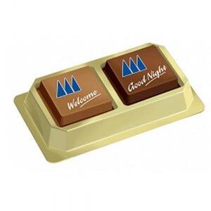 Pralinen bedruckt mit Logo oder Pralinen bedruckt mit Foto verpackt zu 2 Stück in goldener Blisterbox mit Klarsichtdeckel.