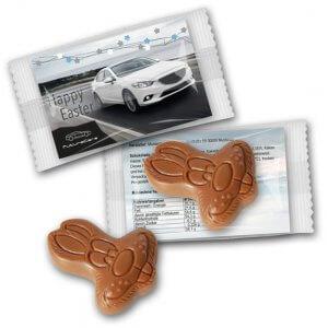 Osterhasenkopf auf Werbekarte aus Schokolade. Osterhase mit Logo bedruckt. Osterhase Werbegeschenk und Werbeartikel Ostern.